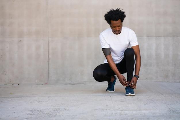 Homem afro-atlético amarrando o cadarço e se preparando para malhar ao ar livre. esporte e conceito de estilo de vida saudável. Foto gratuita