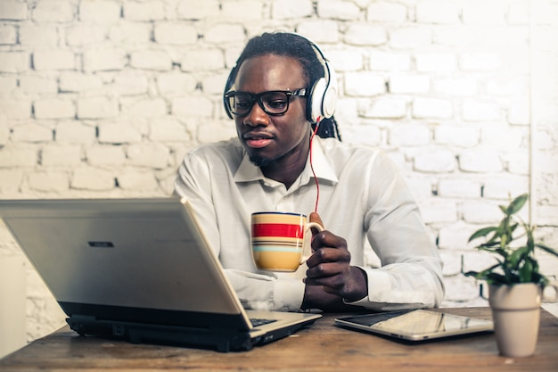 Homem afro bonito, trabalhando em um laptop Foto Premium