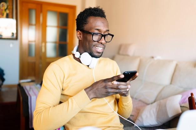 Homem afro em casa com smartphone e laptop Foto Premium