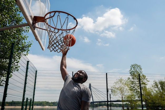 Homem afro, marcando um gol na cesta Foto gratuita