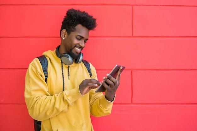 Homem afro usando seu tablet digital com fones de ouvido. Foto gratuita