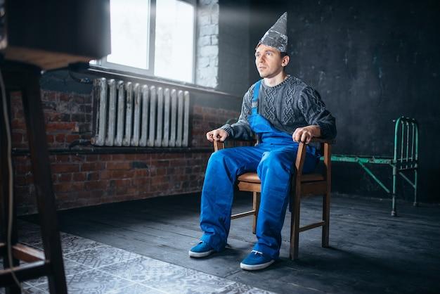 Homem afrontado com capacete de papel alumínio sentado na cadeira Foto Premium