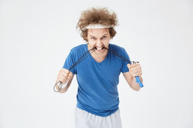 Homem agressivo com roupa esporte brilhante mordendo a corda de pular Foto gratuita