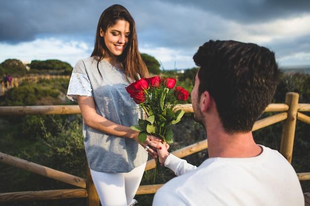 Homem ajoelhado entregar um buquê de rosas para uma mulher Foto gratuita