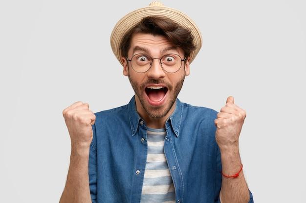 Homem alegre agrônomo aperta os punhos, abre a boca amplamente, exclama de felicidade, usa chapéu de palha e camisa jeans casual, isolado sobre parede branca Foto gratuita