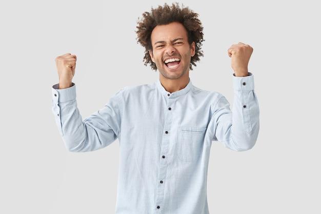 Homem alegre aperta os punhos, tem expressão feliz, grita sim, vestido com roupas brancas Foto gratuita
