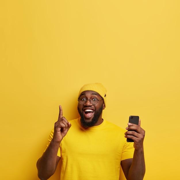 Homem alegre aponta o dedo indicador para cima, cria seu próprio blog, navega na mídia social em um smartphone, tem expressão facial encantada Foto gratuita