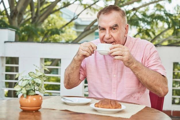 Homem alegre, bebendo café Foto gratuita