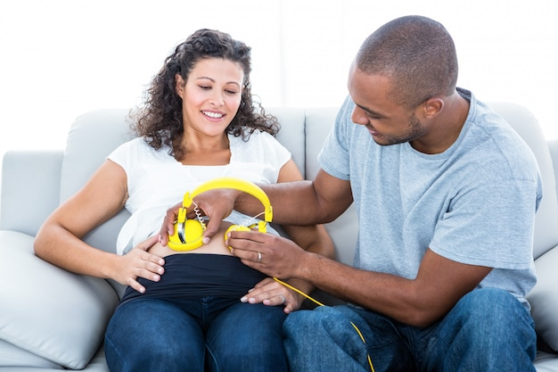 Homem alegre com fones de ouvido na barriga de grávida sentada no sofá em casa Foto Premium