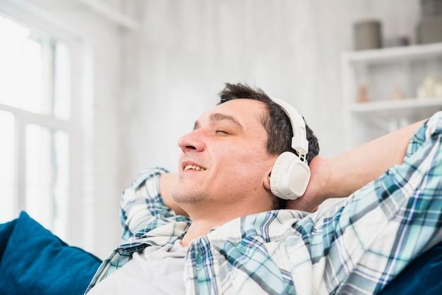 Homem alegre com os olhos fechados, ouvindo música em fones de ouvido no sofá Foto gratuita