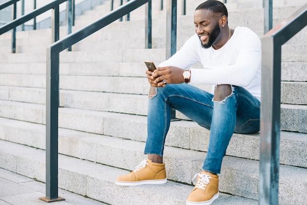 Homem alegre com smartphone nas escadas Foto gratuita