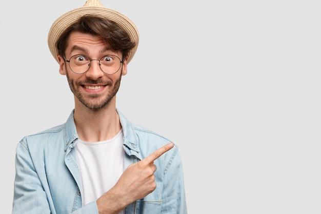 Homem alegre e próspero agricultor com roupas casuais casuais, indica à parte como mostra seu lindo jardim com muitas plantas, sente-se orgulhoso, trabalhando duro, tem expressão feliz Foto gratuita