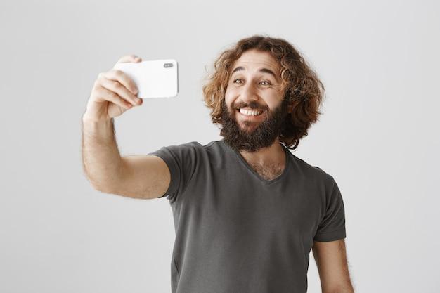 Homem alegre e sorridente do oriente médio tirando uma selfie com smartphone Foto gratuita