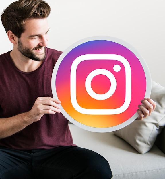 Homem alegre segurando um ícone do instagram Foto gratuita