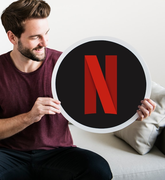 Homem alegre segurando um ícone netflix Foto gratuita