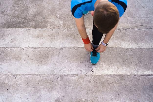 Homem amarrando seus sapatos de desporto em fundo de concreto Foto gratuita