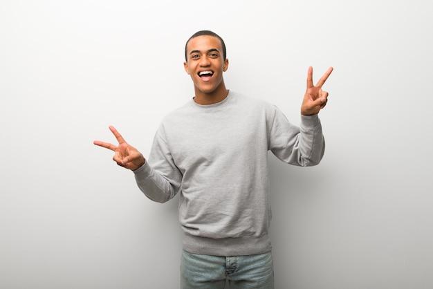 Homem americano africano, branco, parede, fundo, sorrindo, e, mostrando, sinal vitória, com, ambos, mãos Foto Premium