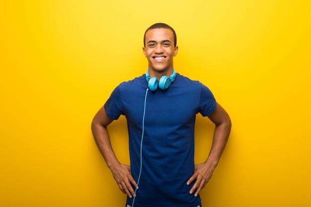 Homem americano africano, com, azul, t-shirt, ligado, experiência amarela, posar, com, braços quadril Foto Premium