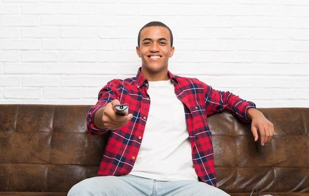 Homem americano africano, com, laptop, em, a, sala de estar, com, um, televisão remoto Foto Premium