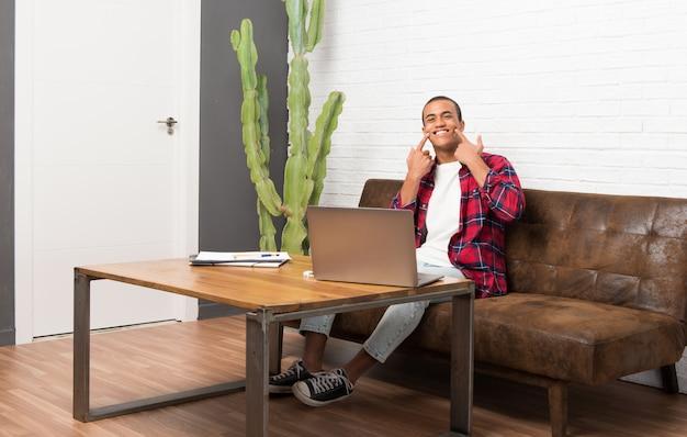 Homem americano africano, com, laptop, em, a, sala de estar, sorrindo, com, um, feliz, e, agradável, expressão Foto Premium