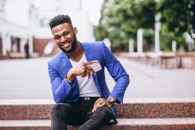 Homem americano africano, em, casaco azul, usando, telefone Foto gratuita
