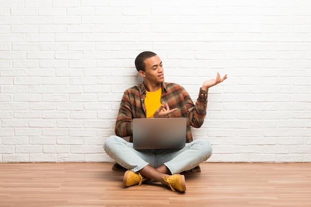 Homem americano africano, sentar chão, com, seu, laptop, estendendo as mãos, para, a, lado, para, convidar, para, venha Foto Premium