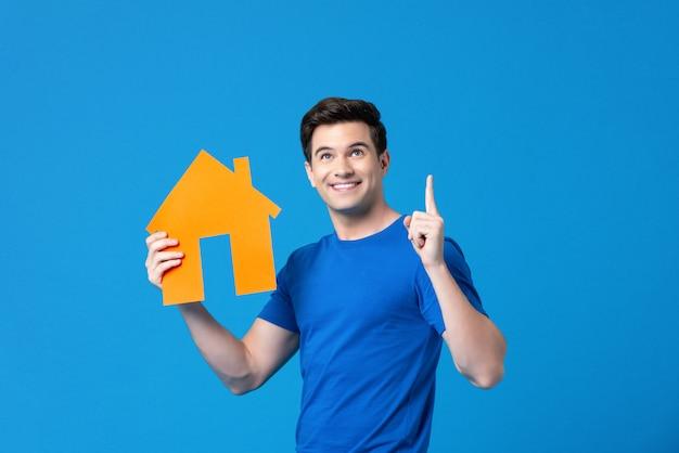 Homem americano bonito atraente segurando um modelo de habitação Foto Premium