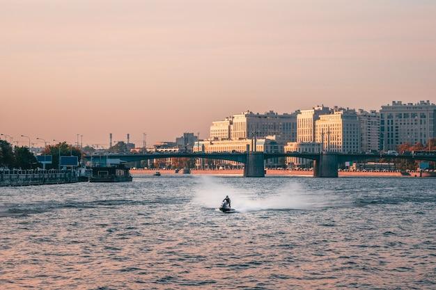 Homem anda de jet ski no rio neva, no centro de são petersburgo. rússia. Foto Premium