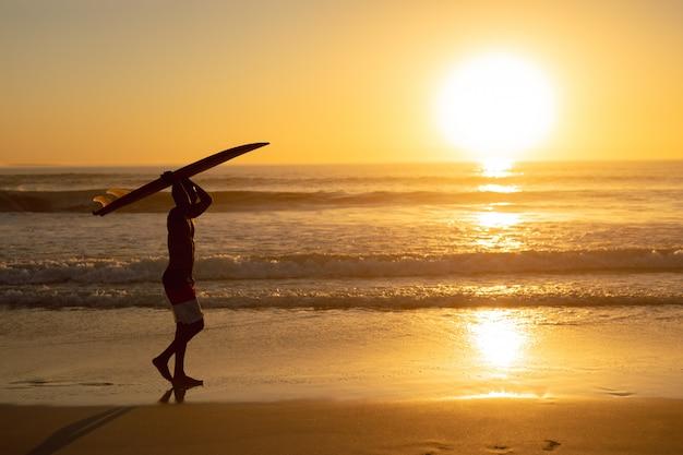 Homem andando com a prancha na cabeça na praia Foto gratuita