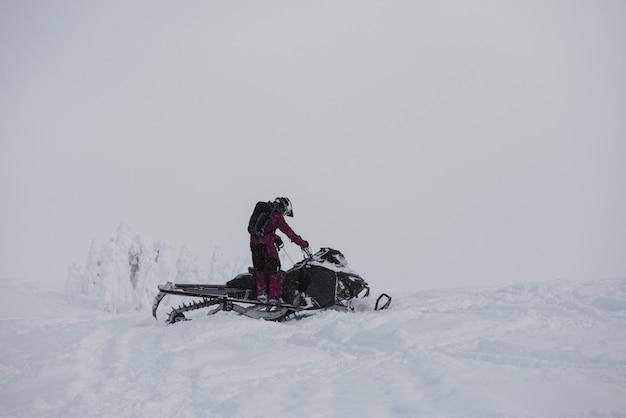Homem andando de moto de neve nos alpes nevados Foto Premium