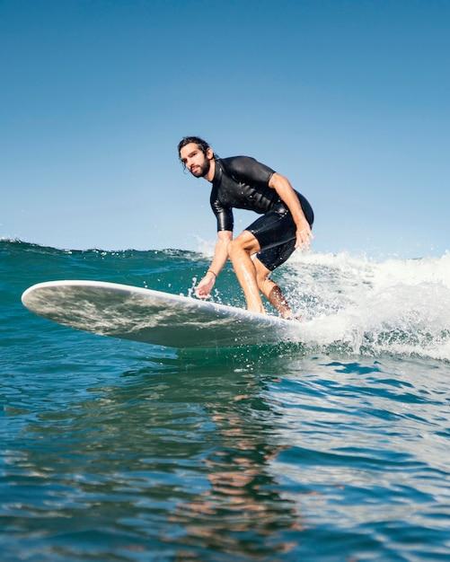 Homem andando de prancha de surf e se divertindo Foto gratuita