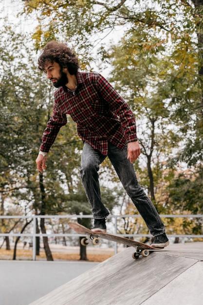 Homem andando de skate no parque da cidade Foto Premium