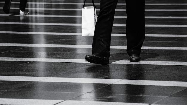 Homem andando na rua depois de fazer compras no urbano - monocromático Foto Premium