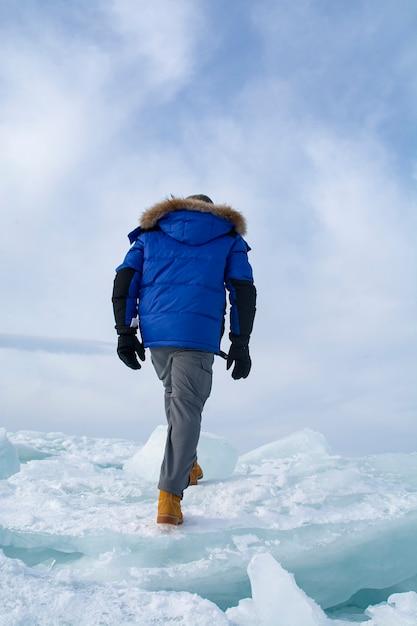 Homem andando no gelo quebrado no lago baikal, rússia Foto Premium