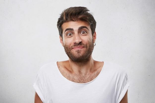 Homem animado com sobrancelhas grossas e escuras e barba, sendo agradavelmente surpreso com os olhos arregalados de olhar duvidoso. foto interna de um cara bonito com uma expressão confusa Foto gratuita