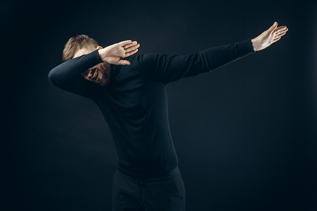 Homem anônimo em roupa elegante preta, cobrindo o rosto com as mãos dançando na parede preta Foto Premium