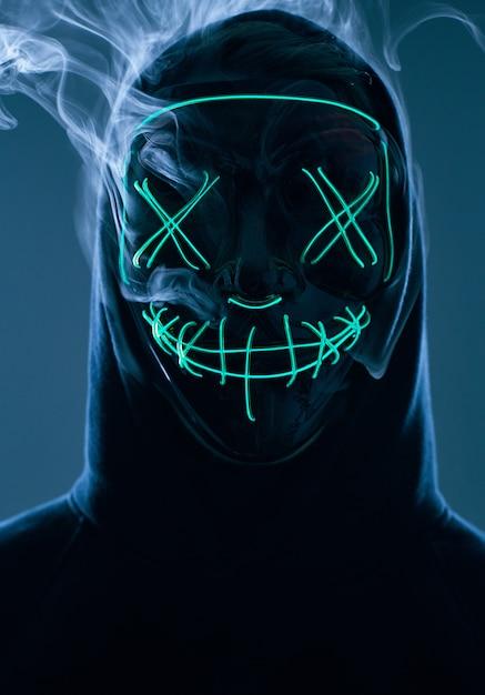 Homem anônimo, escondendo o rosto atrás da máscara de néon em uma fumaça colorida Foto Premium
