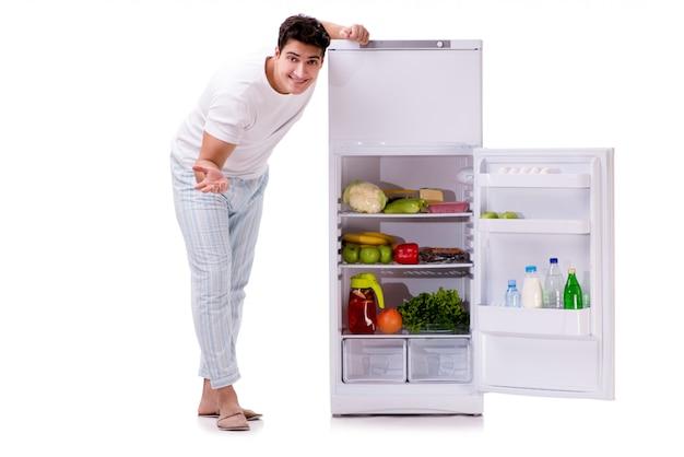 Homem ao lado da geladeira cheia de comida Foto Premium