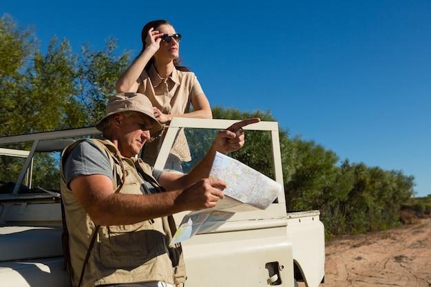 Homem, apontar, enquanto, segurando, mapa, com, mulher, em, veículo Foto gratuita