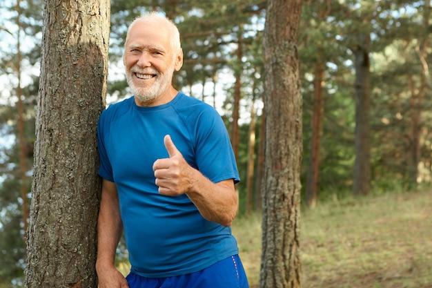 Homem aposentado atraente alegre com cabeça careca e barba grisalha posando ao ar livre com roupas esportivas, sorrindo alegremente, mostrando o gesto de polegar para cima, escolhendo um estilo de vida ativo e saudável, cheio de energia Foto gratuita