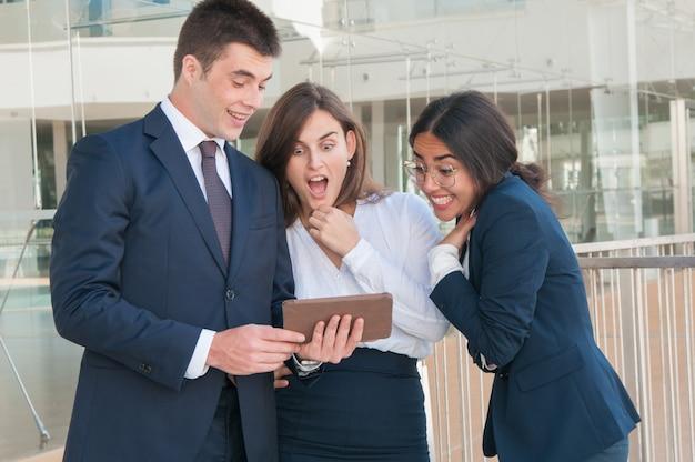 Homem, apresentando, colegas, dados, ligado, tabuleta, eles, olhar, chocado Foto gratuita