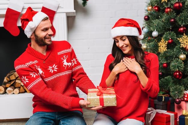 Homem, apresentando, presente, para, mulher, perto, árvore natal Foto gratuita