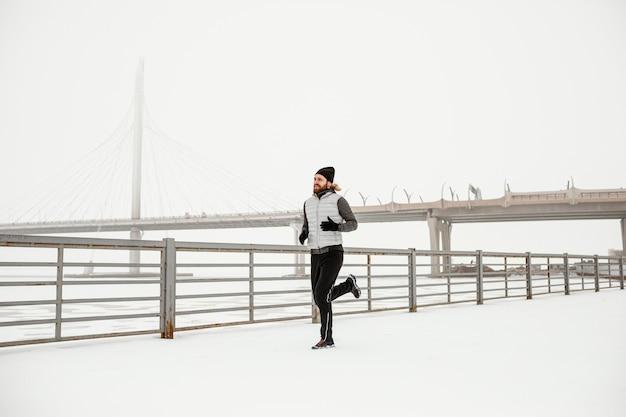 Homem apto correndo ao ar livre em cena completa Foto gratuita