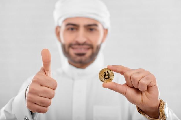 Homem árabe bonito com bitcoin Foto Premium