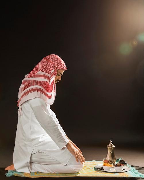 Homem árabe com kandora rezando Foto gratuita