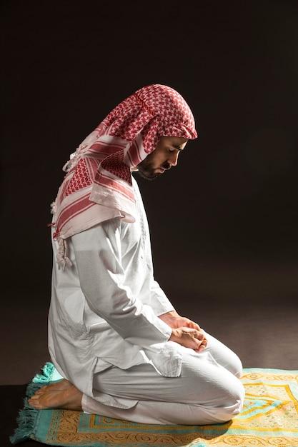 Homem árabe com kandora sentado no tapete de oração para os lados Foto gratuita