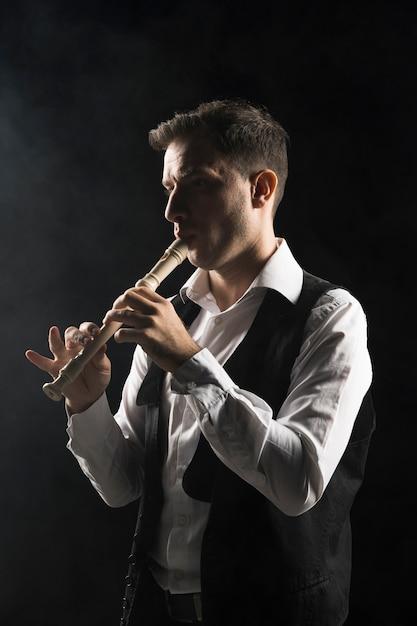 Homem artista no palco tocando flauta Foto gratuita