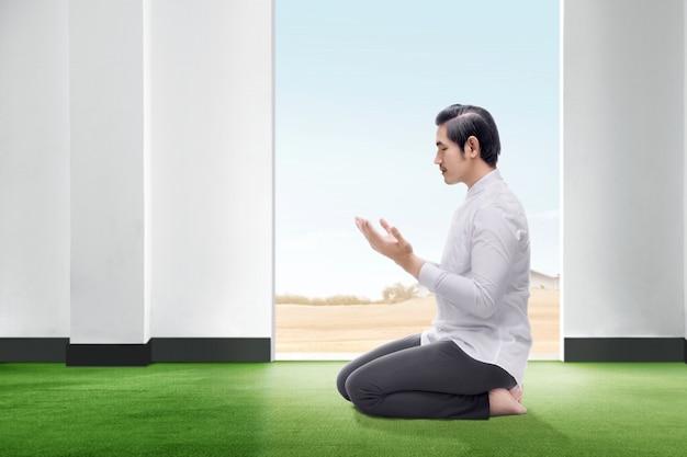 Homem asiático bonito sentado em posição de oração fechar os olhos e levantar as mãos no tapete dentro da sala Foto Premium