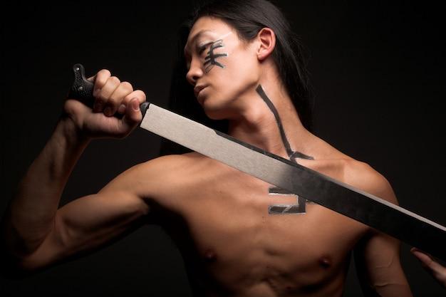 Homem asiático com katana sobre preto Foto Premium