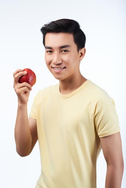 Homem asiático com maçã vermelha Foto gratuita